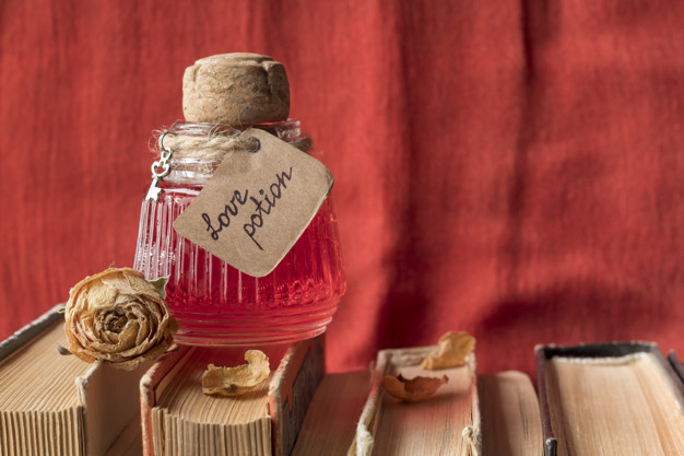 Vintage bottle with magic love potion on spell books against red fabric, space for text. Flask of aphrodisiac. Vial with romantic elixir. Valentine's Day holiday symbol